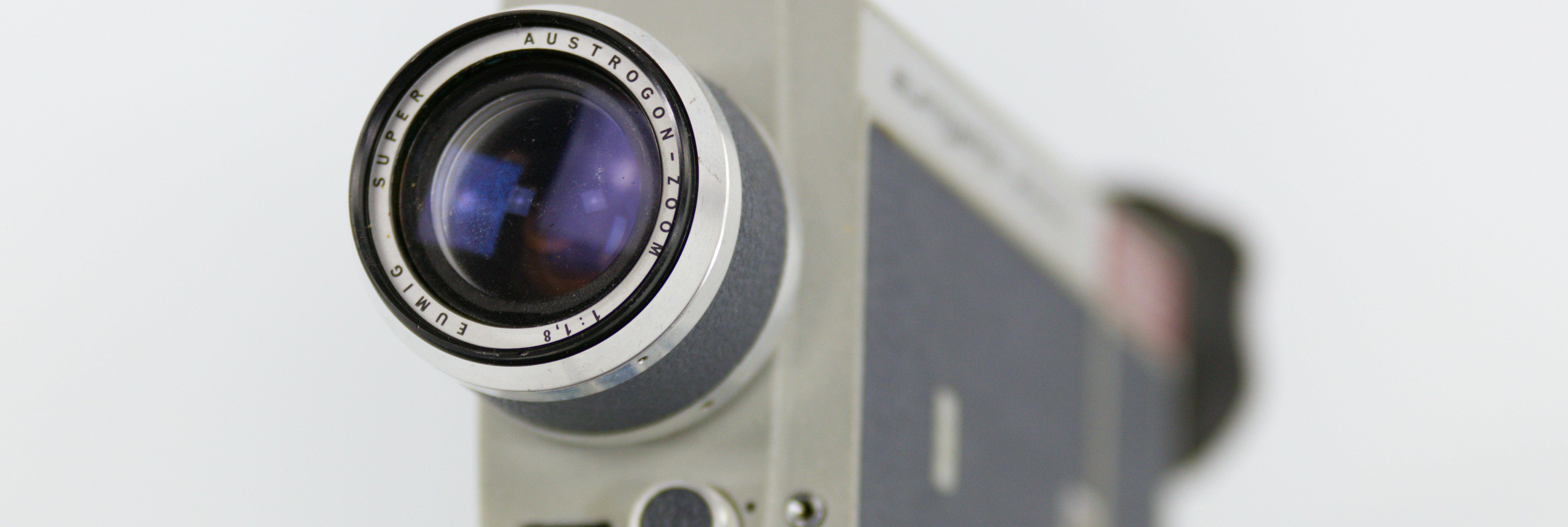 close up of an old fashioned video camera against a white background