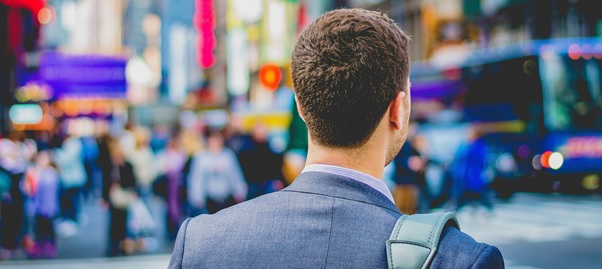 Businessman in blue suit with satchel viewed from behind looking into busy city