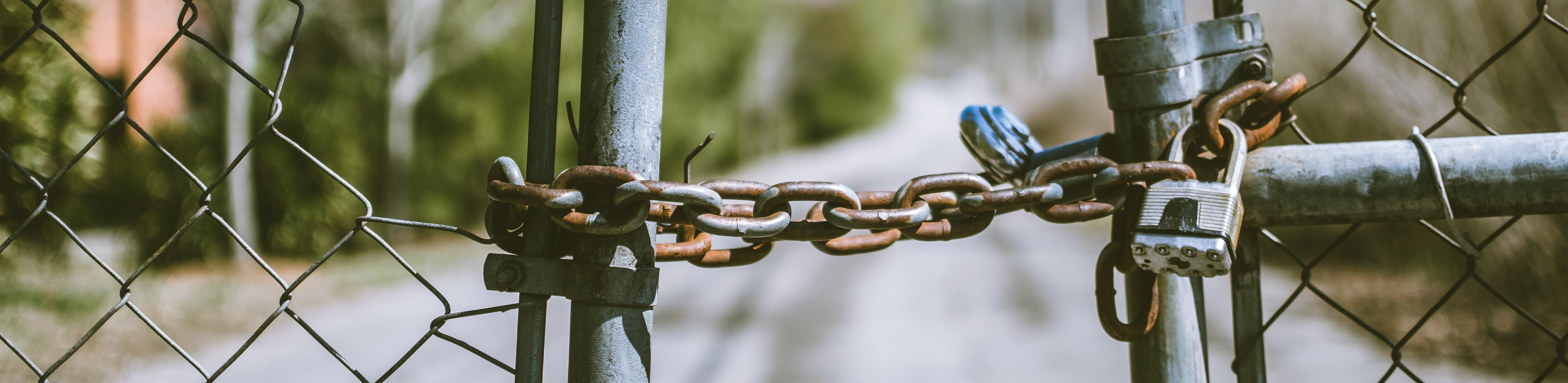 Chainlink gate held shut with a chain and padlock><br></p><p></p><p><br></p>