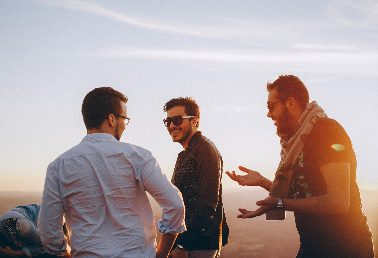 Group of young men laughing and joking on a beach