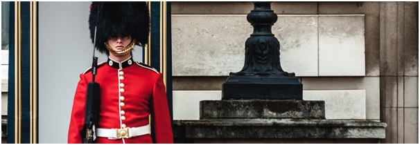 British Army Guardsman in red dress uniform and black busby standing guard at a Royal palace
